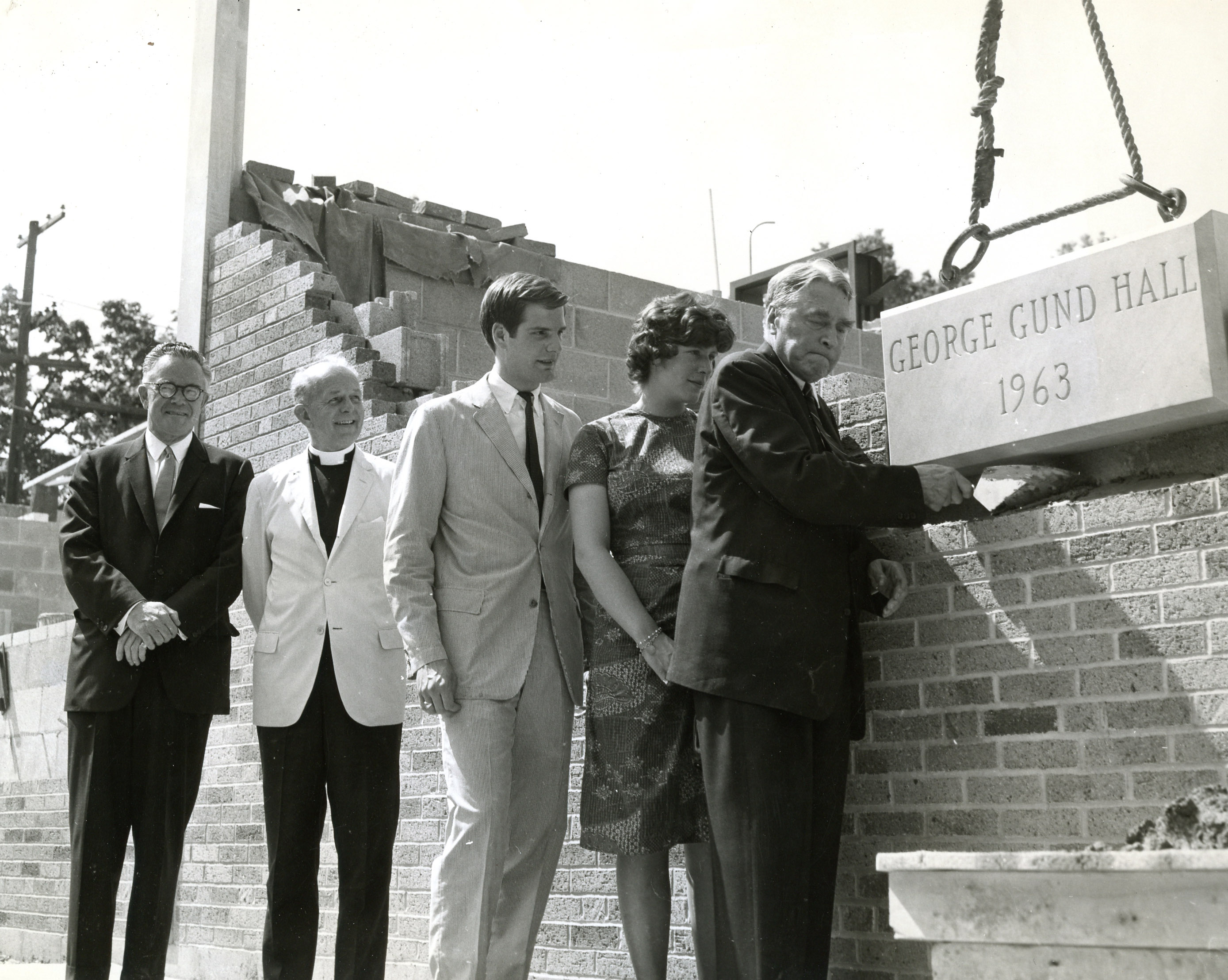 Graham Gund, center, observes his father, George Gund, sealing the cornerstone of Gund Residence Hall in 1963. Photo courtesy of the Greenslade Special Collections and Archives