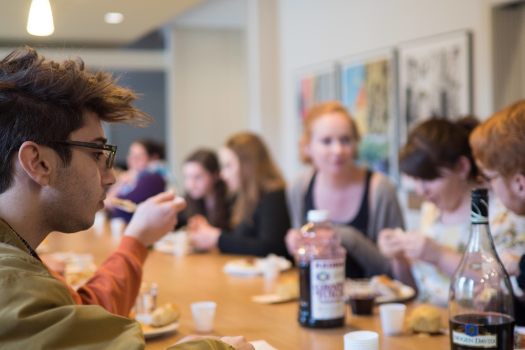 Students in the new Rothenberg Hillel House on Brooklyn Street share a meal at their weekly Shabbat;