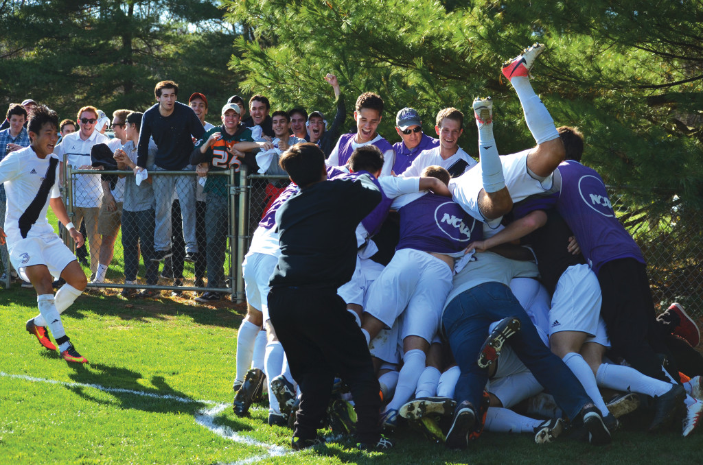 The Lords soccer team dogpiles Philippe Stengel '20 after his title-clinching shot against Oberlin. | Jess Kusher
