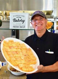 Older man holding a white plate of orange dessert squares.